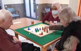 Bewohner*innen und Mitarbeiterin beim Spielen vom Brettspielen