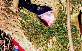 Kind schaut durch Lücke in bemoostem Baum